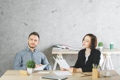 Attraktiver Geschäftsmann und Frau, die Schreibarbeit tut lizenzfreies stockbild