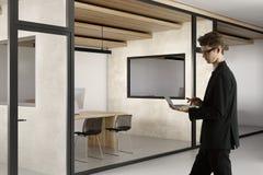 Attraktiver Geschäftsmann unter Verwendung des Laptops im Büro Lizenzfreies Stockbild