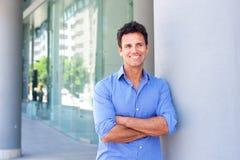 Attraktiver Geschäftsmann, der mit den Armen gekreuzt lächelt Stockfoto