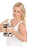 Attraktiver glücklicher Sitz-gesunde junge Blondine, die mit stummen Bell-Gewichten ausarbeiten lizenzfreies stockbild