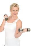 Attraktiver glücklicher Sitz-gesunde junge Frau, die mit stummen Bell-Gewichten ausarbeitet Lizenzfreie Stockfotografie