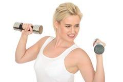 Attraktiver glücklicher Sitz-gesunde junge Frau, die mit stummen Bell-Gewichten ausarbeitet Lizenzfreie Stockbilder