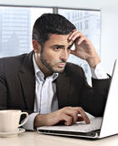 Attraktiver hispanischer Geschäftsmann, der mit dem schauenden Computer betonte und besorgte Einfassungsarbeitsfrage arbeitet lizenzfreie stockfotografie