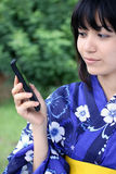 Attraktiver Japaner in einem Kimono mit Mobiltelefon Stockbild