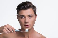 Attraktiver jugendlicher Kerl steht mit Bürste für Zähne lizenzfreie stockfotografie