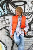 Attraktiver Junge, der an einer Wand sich lehnt Stockfotografie