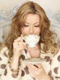 Attraktiver junge Frauen-trinkender Tee im Bett Stockbild