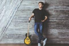 Attraktiver Junge mit Gitarre Stockfoto
