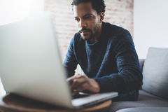 Attraktiver junger afrikanischer Mann, der Laptop beim Sitzen an seinem modernen coworking Platz verwendet Konzept von Geschäftsl stockbilder