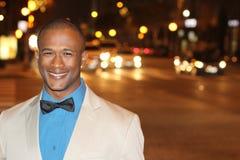 Attraktiver junger afrikanischer Mann nachts mit Stadt beleuchtet hinter ihm, tragender eleganter Anzugsjacke und bowtie mit Kopi Lizenzfreie Stockfotos