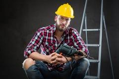 Attraktiver junger Arbeiter mit Bohrgerät lizenzfreie stockfotos