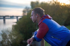 Attraktiver junger athletischer Mann, der auf dem Strand und den Blicken in Abstand von Fluss zur Brücke, hörende Musik steht Lizenzfreies Stockfoto
