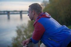 Attraktiver junger athletischer Mann, der auf dem Strand und den Blicken in Abstand von Fluss zur Brücke, hörende Musik steht Lizenzfreies Stockbild