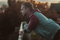 Attraktiver junger athletischer Mann, der auf dem Strand und den Blicken in Abstand von Fluss zur Brücke, hörende Musik steht Stockfotografie