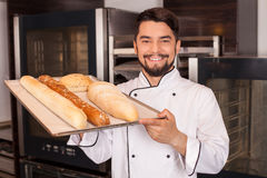 Attraktiver junger Bäcker stellt seine Arbeit dar Stockbilder