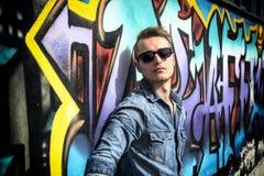 Attraktiver junger blonder Mann gegen bunte Graffitiwand Stockbild