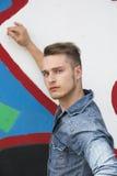 Attraktiver junger blonder Mann gegen bunte Graffitiwand Lizenzfreie Stockfotos