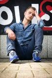 Attraktiver junger blonder Mann gegen bunte Graffitiwand, tragendes Denimhemd Lizenzfreies Stockbild