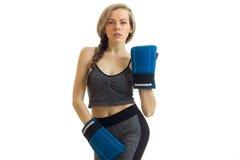 Attraktiver junger blonder Zopf steht in der grauen Sportklage mit Boxhandschuhen und sexy Blicken Lizenzfreies Stockfoto