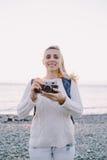 Attraktiver junger Blondinetourist, der mit einer Retro- Kamera in den Händen auf einem Hintergrund von Meer steht Lizenzfreie Stockbilder