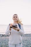 Attraktiver junger Blondinetourist, der mit einer Retro- Kamera in den Händen auf einem Hintergrund von Meer steht Stockfotos