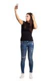 Attraktiver junger Brunette, der hoher Winkel selfie mit ihrem intelligenten Telefon nimmt Lizenzfreie Stockfotografie