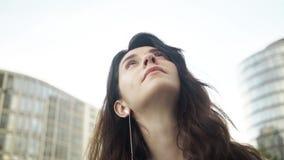 Attraktiver junger Brunette mit den Kopfhörern, die Potsdamer Platz in Berlin betrachten stock video