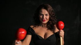 Attraktiver junger Brunettemusiker, der rote maracas spielt stock video