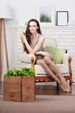 Attraktiver junger dünner Brunette sitzt in einem großen bequemen Stuhl durch den Kamin Stockfoto