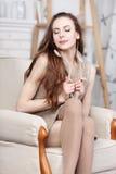 Attraktiver junger dünner Brunette, der in einem großen bequemen Stuhl sitzt Lizenzfreie Stockfotografie