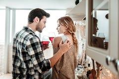 Attraktiver junger dunkelhaariger Mann in einem karierten Hemd und in seiner Frau, die Gläser in ihren Händen halten stockfotos