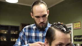 Attraktiver junger Friseur schneidet Menschenhaar mit den Scheren Er betrachtet Haar mit Konzentration Das bärtige stock video