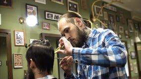 Attraktiver junger Friseur schneidet Menschenhaar mit den Scheren Er betrachtet Haar mit Konzentration Das bärtige stock video footage