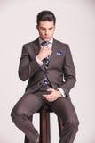 Attraktiver junger Geschäftsmann, der auf einem Schemel sitzt Lizenzfreie Stockbilder