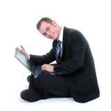 Attraktiver junger Geschäftsmann, der auf Fußboden mit Laptop sitzt Lizenzfreies Stockfoto
