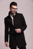 Attraktiver junger Geschäftsmann, der einen eleganten langen Mantel trägt Stockbilder