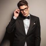 Attraktiver junger Geschäftsmann, der seine Gläser repariert Stockbild