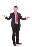 Attraktiver junger Geschäftsmann, der Sie begrüßt Stockbild
