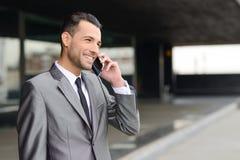 Attraktiver junger Geschäftsmann am Telefon in einem Bürogebäude lizenzfreies stockbild