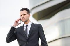 Attraktiver junger Geschäftsmann am Telefon in einem Bürogebäude stockfoto