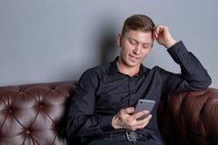 Attraktiver junger gut aussehender Mann, der schwarzes Hemdsitzen auf dem ledernen Sofaholding Smartphone tr?gt Komfort und Entsp lizenzfreie stockfotos