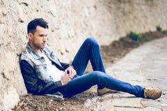 Attraktiver junger gutaussehender Mann, Baumuster der Mode im städtischen backgro stockfoto