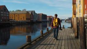 Attraktiver junger hübscher Tourist mit einem gelben Rucksack gehend in das Stadtzentrum und ein Foto, Zeitlupe machend stock footage