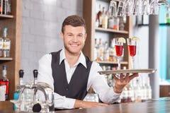 Attraktiver junger Kellner dient Kunden herein Stockbild