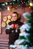 Attraktiver junger Mann in den Weihnachtsdekorationen Weihnachten Neues Jahr Stockbild
