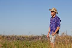 Attraktiver junger Mann, der auf einem Gebiet steht cowboy stockfotos