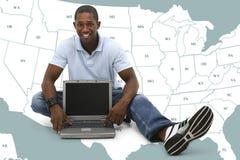 Attraktiver junger Mann, der auf Fußboden mit Laptop-Computer sitzt Lizenzfreies Stockbild