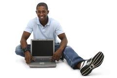 Attraktiver junger Mann, der auf Fußboden mit Laptop-Computer sitzt Lizenzfreies Stockfoto