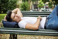 Attraktiver junger Mann, der auf Holzbank schläft Stockfoto