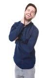 Attraktiver junger Mann, der auf lokalisiertem weißem Hintergrund lächelt Stockbilder